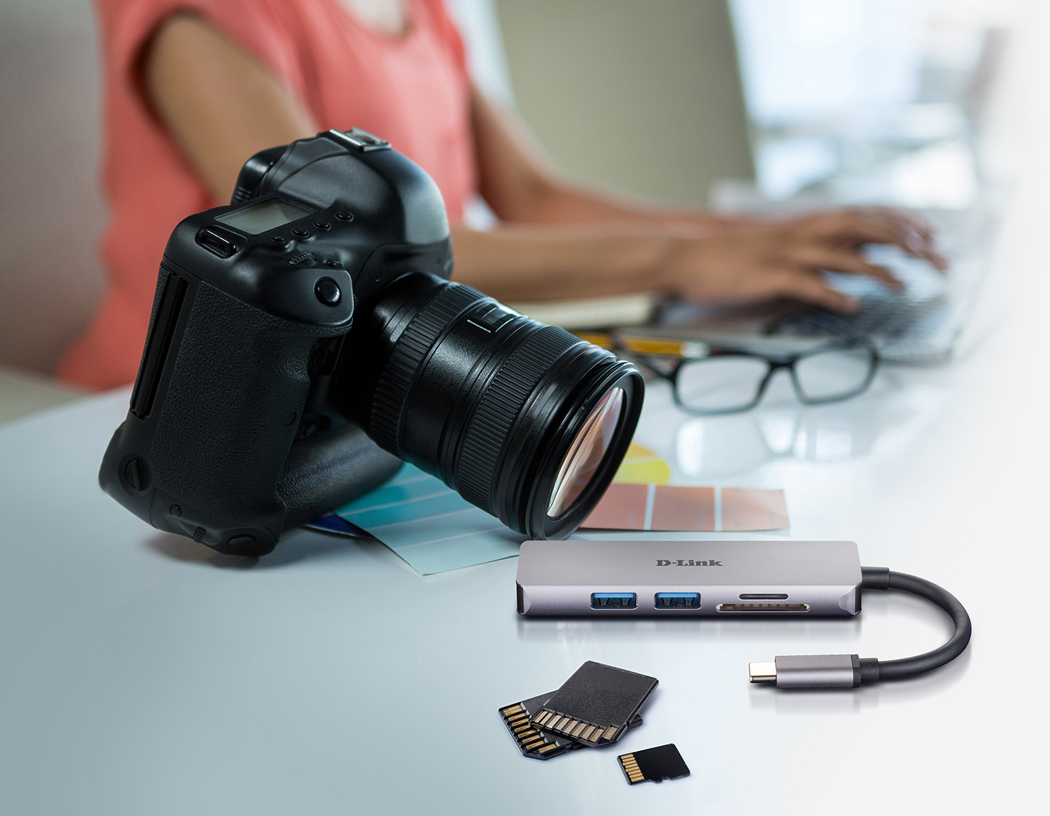 DUB-M530 5-in-1 USB-C Hub with HDMI/Card Reader next to a camera