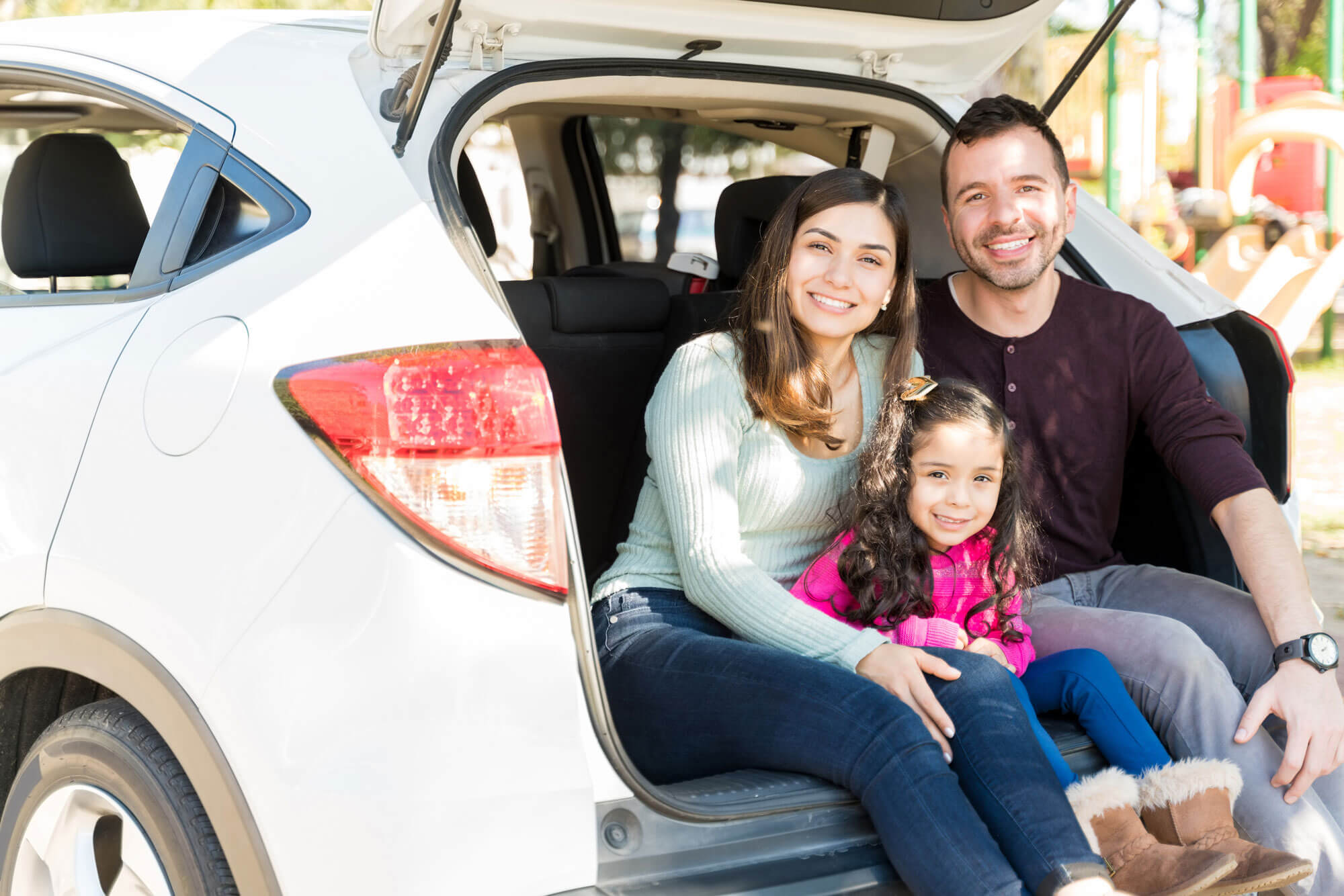 A smiling family sat in the boot of a car