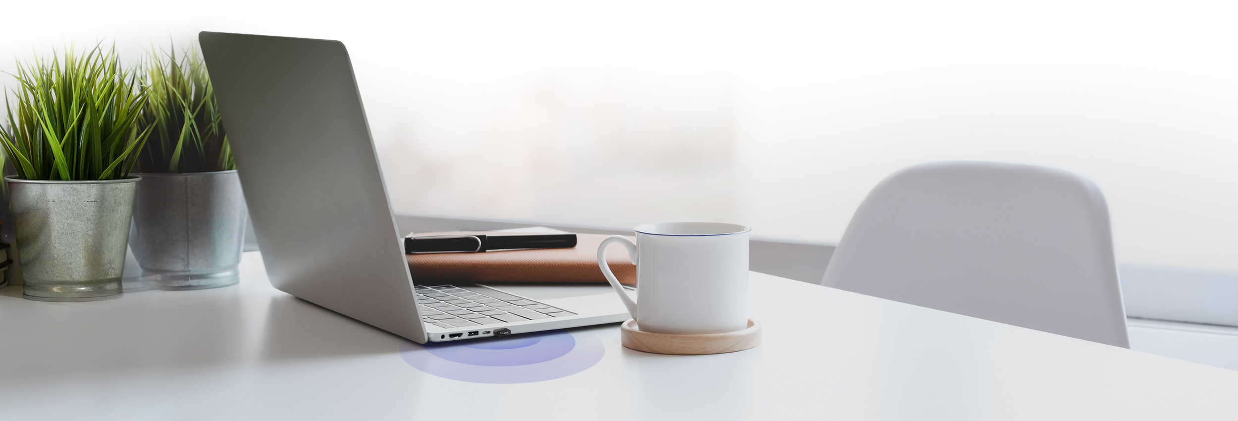 DWA-181 AC1300 MU-MIMO Wi-Fi Nano USB Adapter  connected to a laptop beside coffee cup on a table