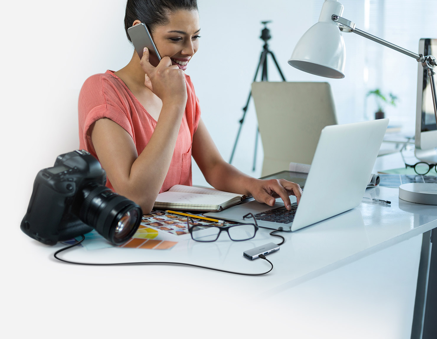 Woman using the DUB-M530 5-in-1 USB-C Hub with HDMI/Card Reader connected to a laptop and a camera