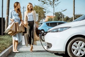Shoppers looking at a charging car in a car park.